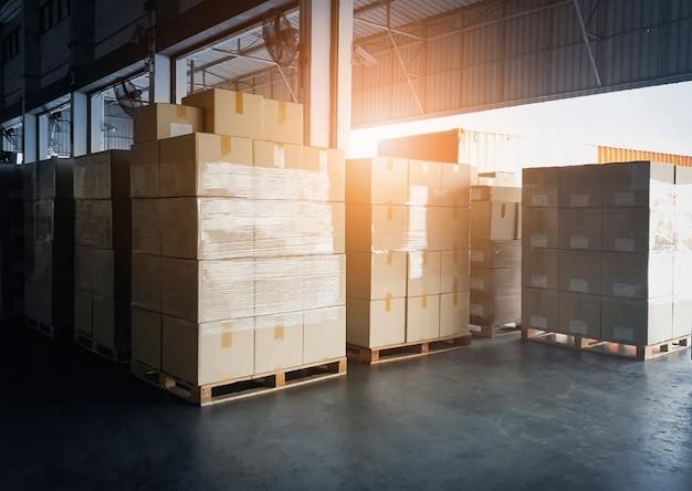 Pila di scatole di cartone in attesa di carico nel container del camion. servizio di deposito merci, spedizione, consegna. Foto Premium