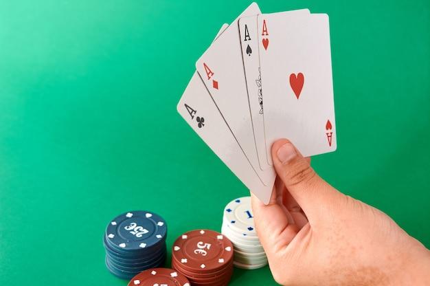 Pila di fiches e mano con quattro assi, panno da poker, un mazzo di carte, mano di poker e fiches. sfondo. Foto Premium
