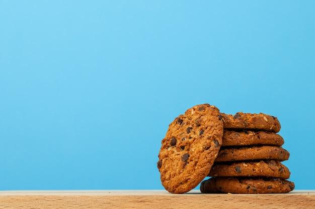 Pila di biscotti al cioccolato su sfondo blu Foto Premium