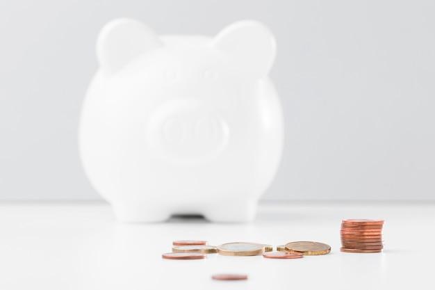 Pila di monete accanto al porcellino salvadanaio Foto Premium