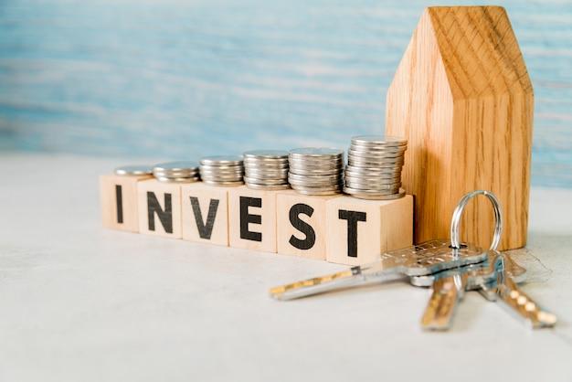 La pila di monete sopra investe i blocchi di legno vicino al modello della casa con le chiavi d'argento sulla superficie di bianco Foto Premium