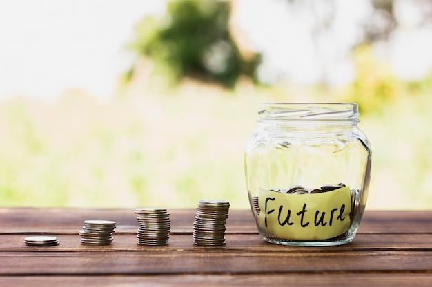 Pila di monete e barattolo con risparmio Foto Premium