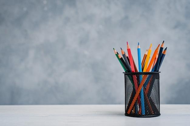 Una pila di libri di testo colorati e un bicchiere di matite luminose su un tavolo grigio-blu. concetto di istruzione, formazione, area di lavoro, spazio libero. Foto Premium