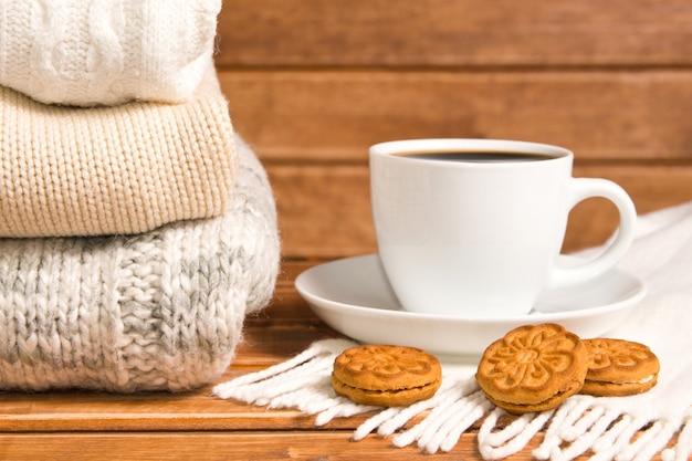 Pila di maglione caldo lavorato a maglia accogliente, fondo di legno. Foto Premium