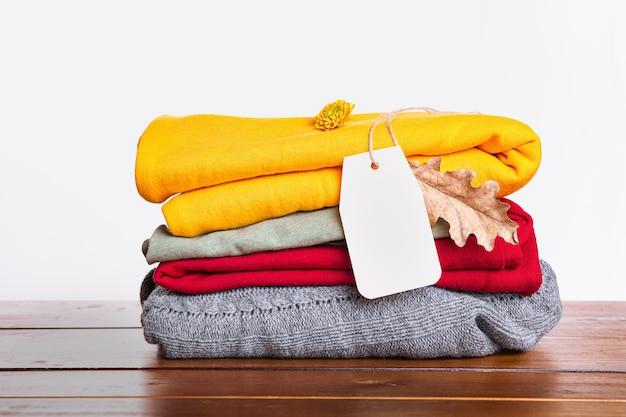 Una pila di maglioni autunno-inverno rossi, grigi, gialli su un tavolo di legno e su uno sfondo bianco. vestiti caldi e accoglienti. Foto Premium