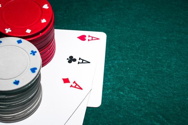 Pila di fiches del casinò bianco e rosso sopra i tre assi sul tavolo da poker Foto Premium