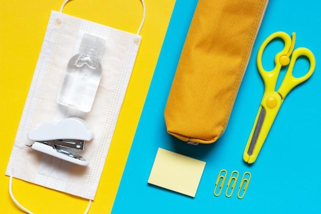 Cancelleria e mascherina medica su una vista dall'alto di sfondo giallo e blu Foto Premium
