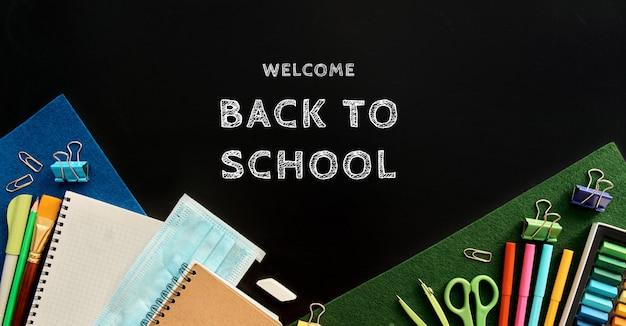 Articoli di cancelleria su sfondo nero. forniture scolastiche vista dall'alto per pubblicità e articoli promozionali. torna al concetto di scuola Foto Premium