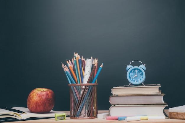 Articoli di cancelleria e accessori colore gesso, pastello, gomma, matita, righello, rosso mela, libro, mettere sulla lavagna cancelleria in legno scrivania vuota sullo sfondo di aula. istruzione torna al concetto di scuola Foto Premium