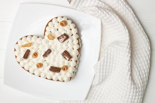 Istruzioni dettagliate per la ricetta della torta a forma di cuore. decorate la torta con gocce di cioccolato, waffle, biscotti. lay piatto. Foto Premium