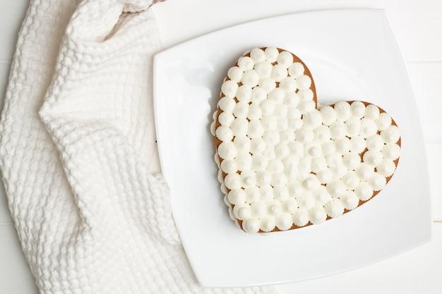 Istruzioni dettagliate per la ricetta della torta a forma di cuore. passaggio 11: mettere le torte con la crema una sopra l'altra, adagiarle. Foto Premium