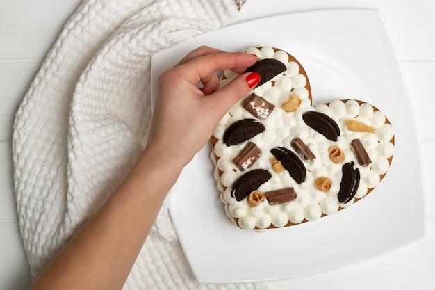 Istruzioni dettagliate per la ricetta della torta a forma di cuore. passaggio 12: decorare la torta con gocce di cioccolato, waffle, biscotti. lay piatto. Foto Premium