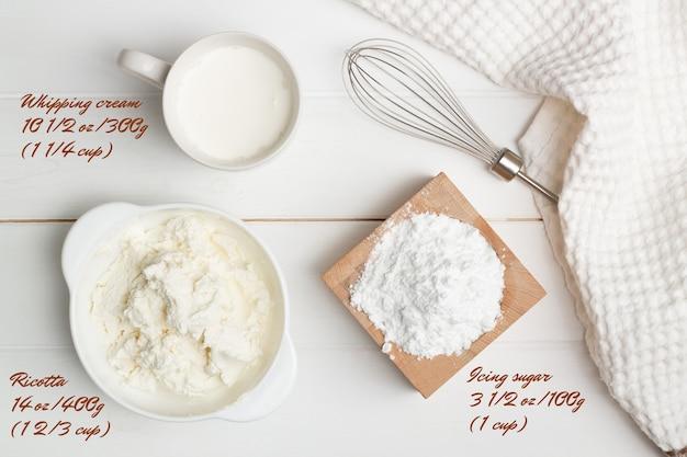 Istruzioni dettagliate per la ricetta della torta a forma di cuore. passaggio 6, ingredienti per la crema. zucchero a velo, ricotta, panna da montare. lay piatto. Foto Premium