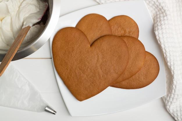 Istruzioni dettagliate per la ricetta della torta a forma di cuore. passaggio 8: cuocere le torte per 10 minuti a 180 ° c, adagiarle. Foto Premium