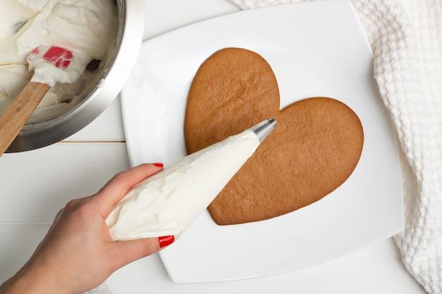 Istruzioni dettagliate per la ricetta della torta a forma di cuore. passaggio 9: mettere la crema in una sac à poche, adagiarla. Foto Premium