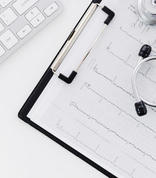 Stetoscopio su elettrocardiografo sopra la lavagna per appunti e laptop su sfondo bianco Foto Premium