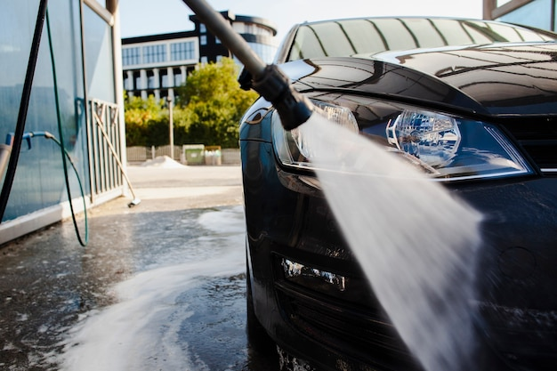 Stick lavare la parte anteriore di un'auto con acqua Foto Premium