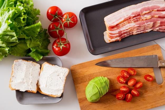 Composizione di natura morta composta da due panini, pomodori freschi, lattuga, avocado e vassoio con fette di pancetta sul tavolo della cucina Foto Premium