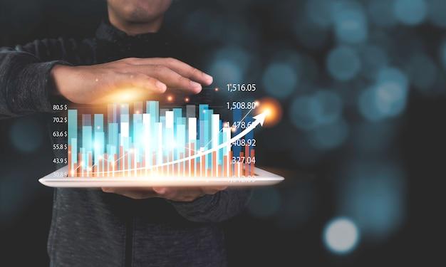 Compressa della tenuta dell'investitore di riserva che che mostra il grafico e il grafico tecnici di fantasia virtuale con la freccia. profitto aziendale e concetto di crescita dei dividendi. Foto Premium