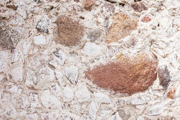 Trama di muro di pietra. fondo decorativo della parete delle rocce del mosaico. muro in muratura di vecchie pietre. rivestimento decorativo delle pareti esterne della casa. Foto Premium