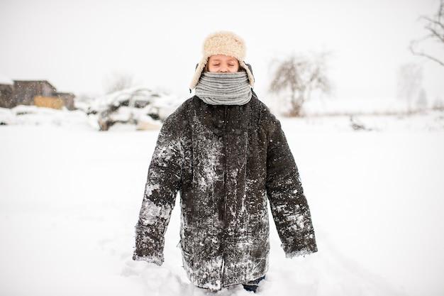 Strana bambina in abiti oversize usurati in piedi sulla strada innevata in una giornata invernale nel villaggio russo Foto Premium
