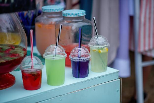 In un festival del cibo di strada, cocktail colorati vengono esposti sul bancone in bicchieri usa e getta con cannucce, fumando dal ghiaccio artificiale all'interno. sangria di vino, limonate fatte in casa. Foto Premium