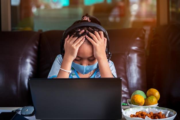 Lo stress bambina della scuola è studio a casa con il computer portatile e la maschera. concetto di formazione online Foto Premium
