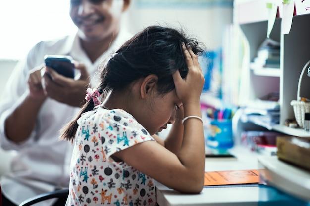 Ragazza stressata del bambino che si siede con le mani che tengono la testa. perché suo padre non era interessato Foto Premium