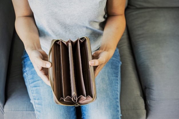 La giovane donna sollecitata apre il suo portafoglio vuoto a casa Foto Premium