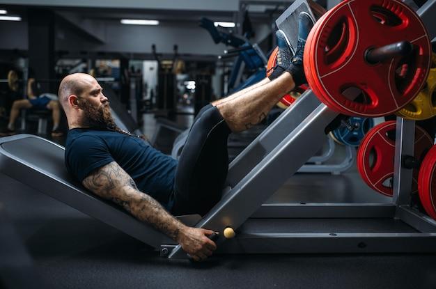 Forte atleta sulla macchina ginnica con bilanciere, allenamento in palestra. Foto Premium
