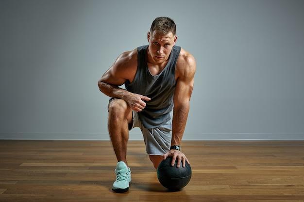 Uomo forte che fa esercizio con la palla medica. foto del fisico perfetto dell'uomo su fondo grigio. forza e motivazione. Foto Premium