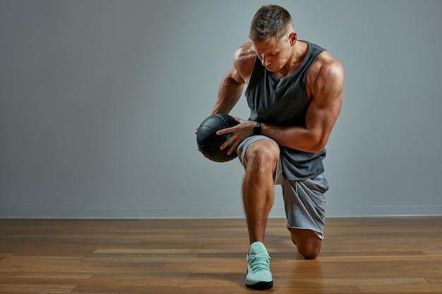 Uomo forte che fa esercizio con la palla medica. foto del fisico perfetto dell'uomo sulla parete grigia. forza e motivazione. Foto Premium