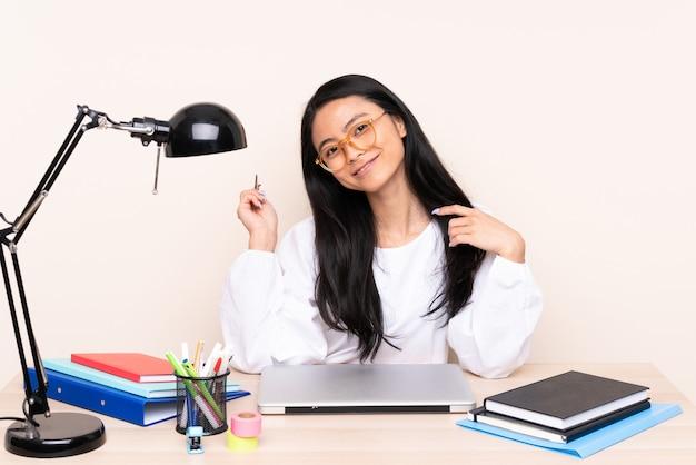 Ragazza asiatica dell'allievo in un posto di lavoro con un computer portatile isolato sul beige Foto Premium