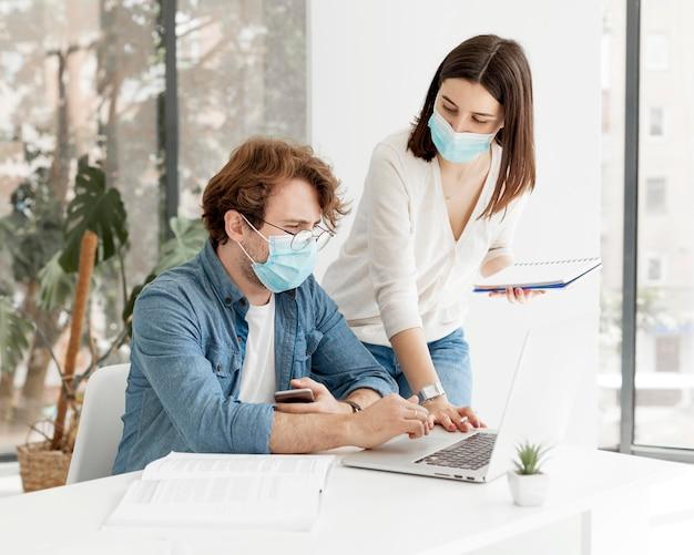 Studente e tutor che indossano maschere mediche Foto Premium