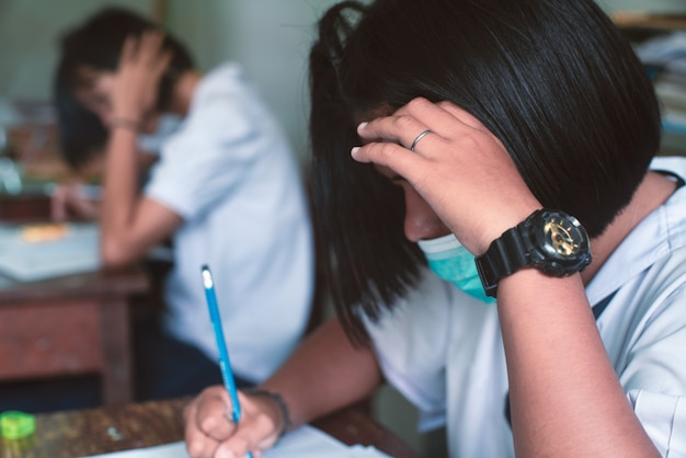 Gli studenti che indossano la maschera per proteggere il virus corona o il covid-19 e che fanno i fogli di risposta agli esami si esercitano in aula con stress. Foto Premium