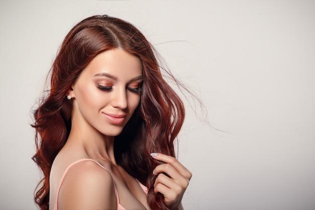 Studio glamour ritratto di una bella donna con i capelli lussuosi su uno sfondo chiaro. posto per copyspace. Foto Premium