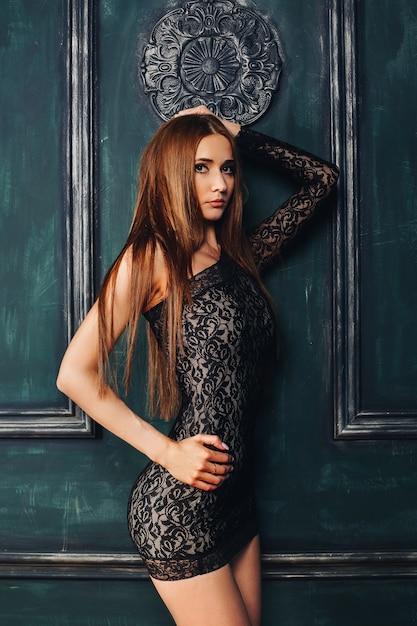 Ritratto dello studio della ragazza sottile seducente che porta mini vestito nero sexy che posa sopra la parete del pannello di legno dell'annata Foto Premium