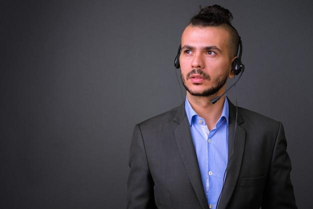 Studio shot di bell'uomo d'affari turco che indossa la cuffia che lavora come rappresentante del call center su sfondo grigio Foto Premium