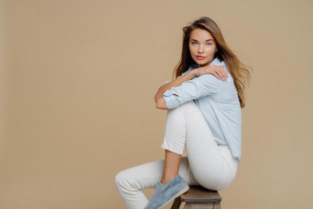 Lo studio ha sparato di bella donna caucasica riposante si siede sulla sedia, indossa camicia, pantaloni bianchi e scarpe Foto Premium