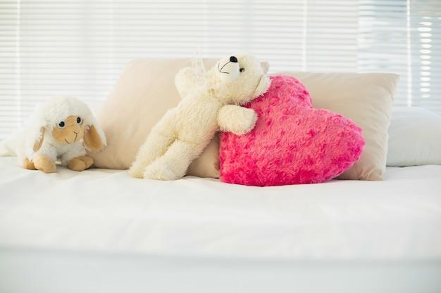 Animali imbalsamati e un cuscino cuore sdraiato sul divano Foto Premium