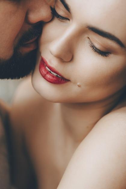 Splendida ragazza caucasica con labbra rosse è baciata dal suo amante barbuto mentre si abbracciano Foto Premium