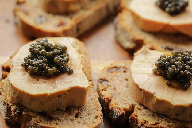 Caviale nero di storione su foie gras e pane da taglio, concetto di celebrazione fevtive Foto Premium