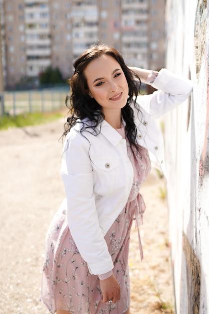 Ritratto di stile di giovane bella donna elegante sorridente felice che cammina alle strade della città. Foto Premium