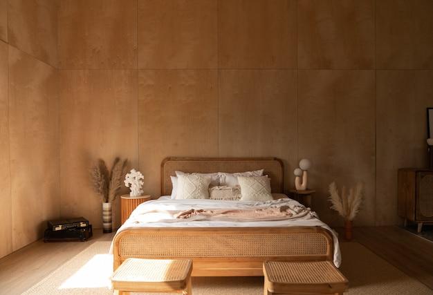 Elegante angolo camera da letto con testiera in rattan e letto con morbidi cuscini bianchi con pareti in compensato Foto Premium