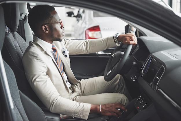 Uomo d'affari nero alla moda che si siede al volante della nuova auto di lusso. ricco uomo afroamericano Foto Premium