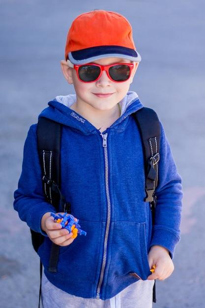 Ragazzo alla moda in occhiali da sole con il giocattolo in mano Foto Premium
