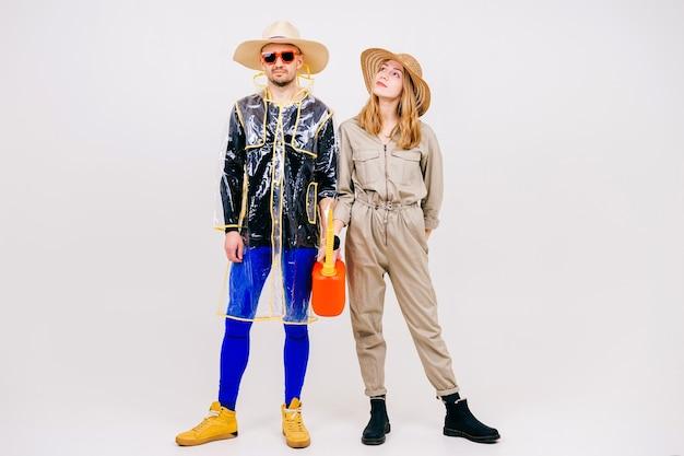 Elegante coppia di uomo e donna in cappelli di paglia in posa con annaffiatoio Foto Premium