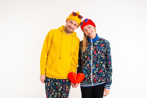 Elegante coppia carina di un uomo e di una donna in abiti colorati che tengono il cuore Foto Premium