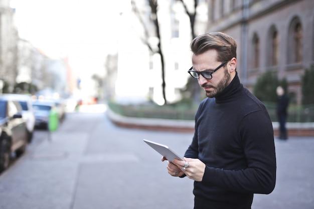 Uomo alla moda che per mezzo di un tablet sulla strada Foto Premium