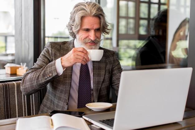 Elegante maschio maturo che gode del caffè in ufficio Foto Premium